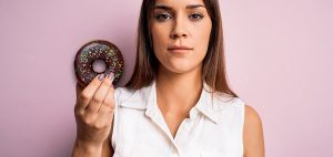 Woman holds up a donut